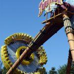 People on a large spinning pendulum.