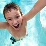 A boy smiling in the water.