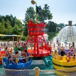 People playing in a water park tea cup ride.