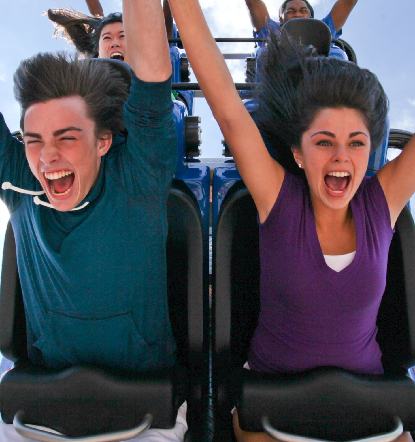 People riding on a coaster with their hands in the air.