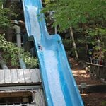 A person launching down a blue water slide.