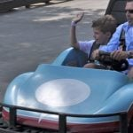 Kids smiling riding go-carts.