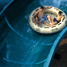 People on a float tube sliding down a water slide.