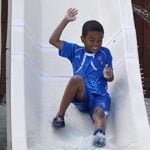 A kid going down a waterslide.