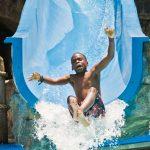 A boy sliding into a pool.