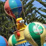 A statue looking through binoculars on a hot air balloon.