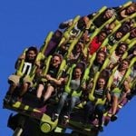 People on a roller coaster with their hands in the air.