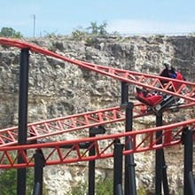 Guests on a red roller coaster.