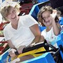 Kids riding on a small roller coaster.
