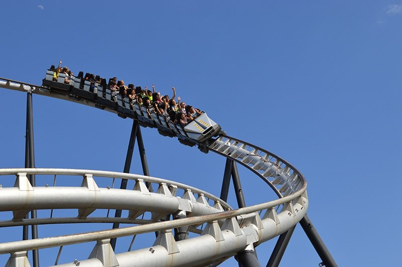 Guests riding on the silver bullet with their hands in the air.