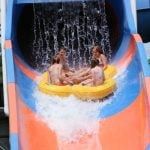 Four people on a tube on a water slide.