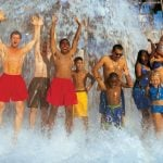 A giant bucket of water dumping on a group of people.