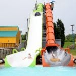 Kids going down a green and orange water slide.