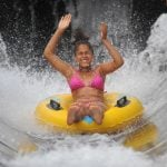 Person in a tube coming out of waterslide.