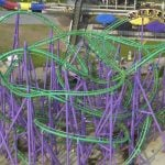 People riding a purple and green roller coaster.