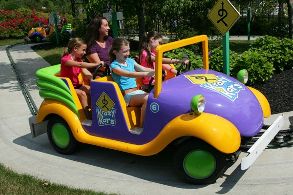 Kids driving purple and yellow track cars