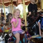 A kid riding on the carousel.