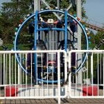 Slingshot ride empty in front of trees.