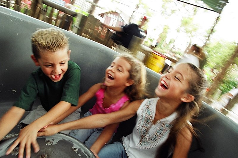 Three kids laughing and smiling twirling a teacup ride.