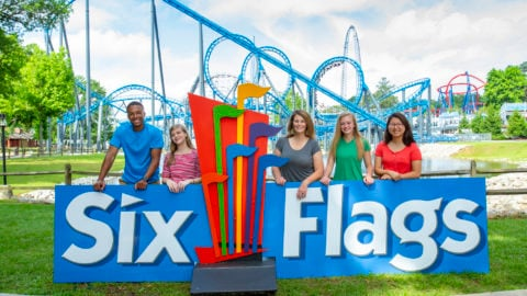 group posing for picture at six flags sign