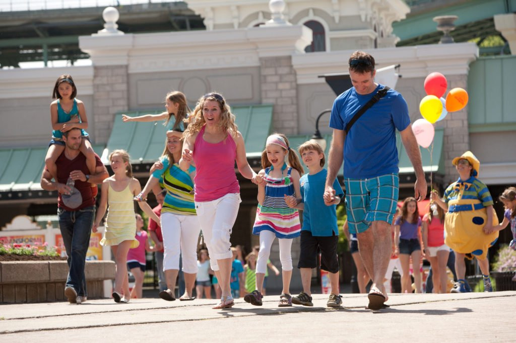 A family walking through the Six Flags theme park