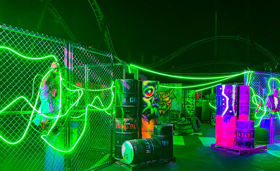 green neon lights with glowing barrels in Deadzone at Six Flags Magic Mountain