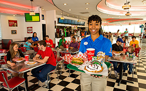 Employee smiling and holding a tray of food at Six Flags