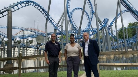 group of three posing in front of rollercoaster