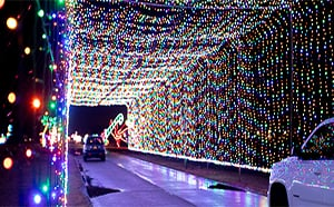 Tunnel of lights with car going through it