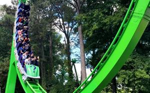 THE RIDDLER Mindbender rollercoaster train speeding through a bright green loop