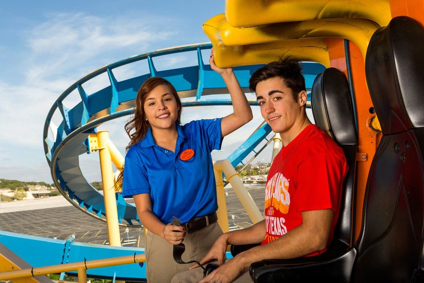 Guest sitting in ride vehicle with employee checking the safety restraints