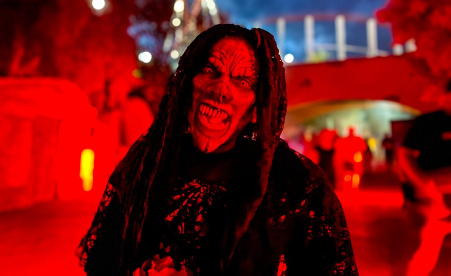 A scary ghoul lit with red lights at Six Flags Magic Mountain