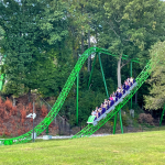 THE RIDDLER Mindbender rollercoaster train rushing guests down a steep hill