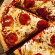 Cooked pepperoni pizza with slice being removed.