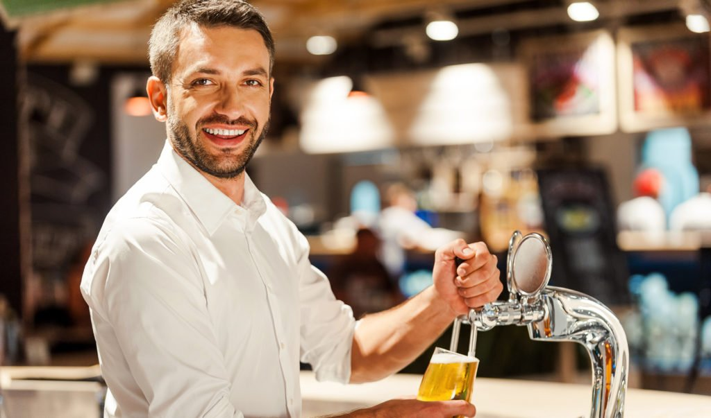 bartender smiling and pouring beer