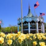 Columbia Carousel with American flags and flowers in front at Six Flags