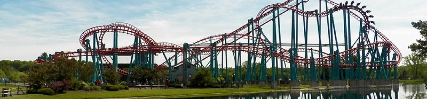 Roller coaster in front of body of water.