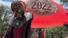 a creepy character standing in front of a 2022 balloon at six flags