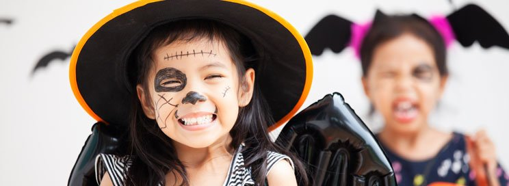 young girl dressed as witch smiling