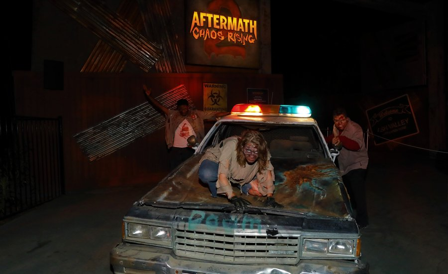 Zombies on old rusty car in from of aftermath of chaos
