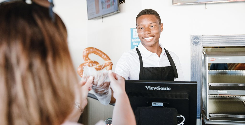 an employee smiling while handing a guest a large pretzel