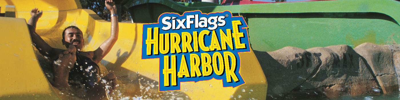 A guests sliding down a yellow water slide with the hurricane harbor logo