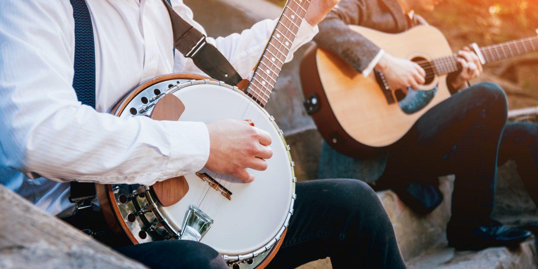 closeup of a man playing banjo and a man playing guitar at Six Flags