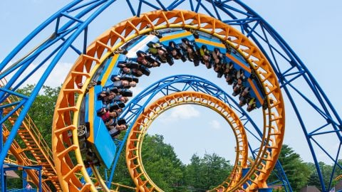 Guests spiraling through the blue and yellow Steamin Demon coaster at Six Flags
