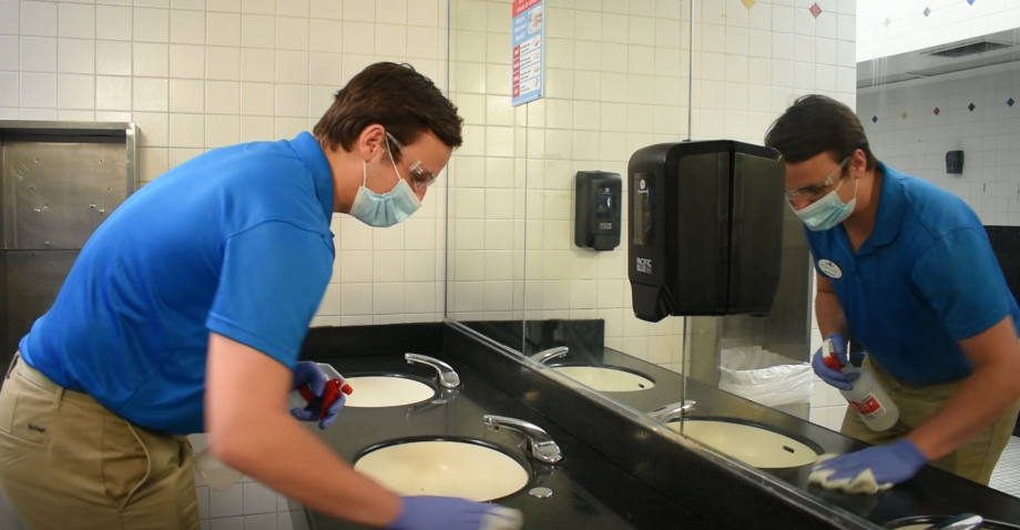 a masked employee sanitizing a bathroom at six Flags