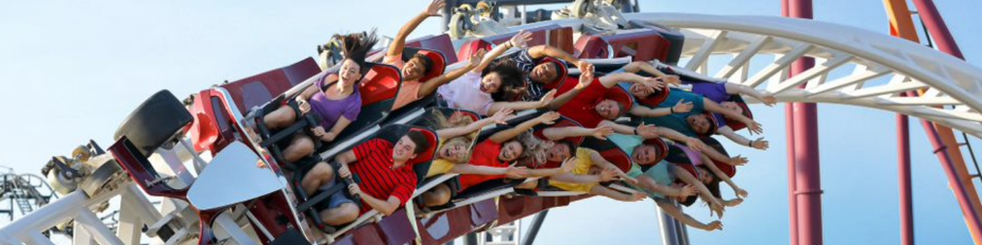 Guests riding a coaster at Six Flags and smiling
