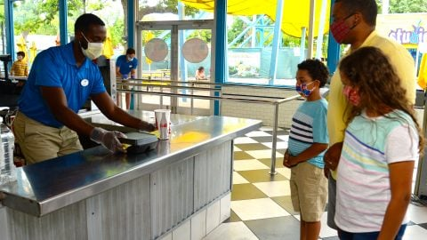 six flags employee helping guests at the park