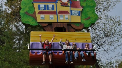 kids with their hands in the air smiling while riding Hootie's Treehouse at The Great Escape