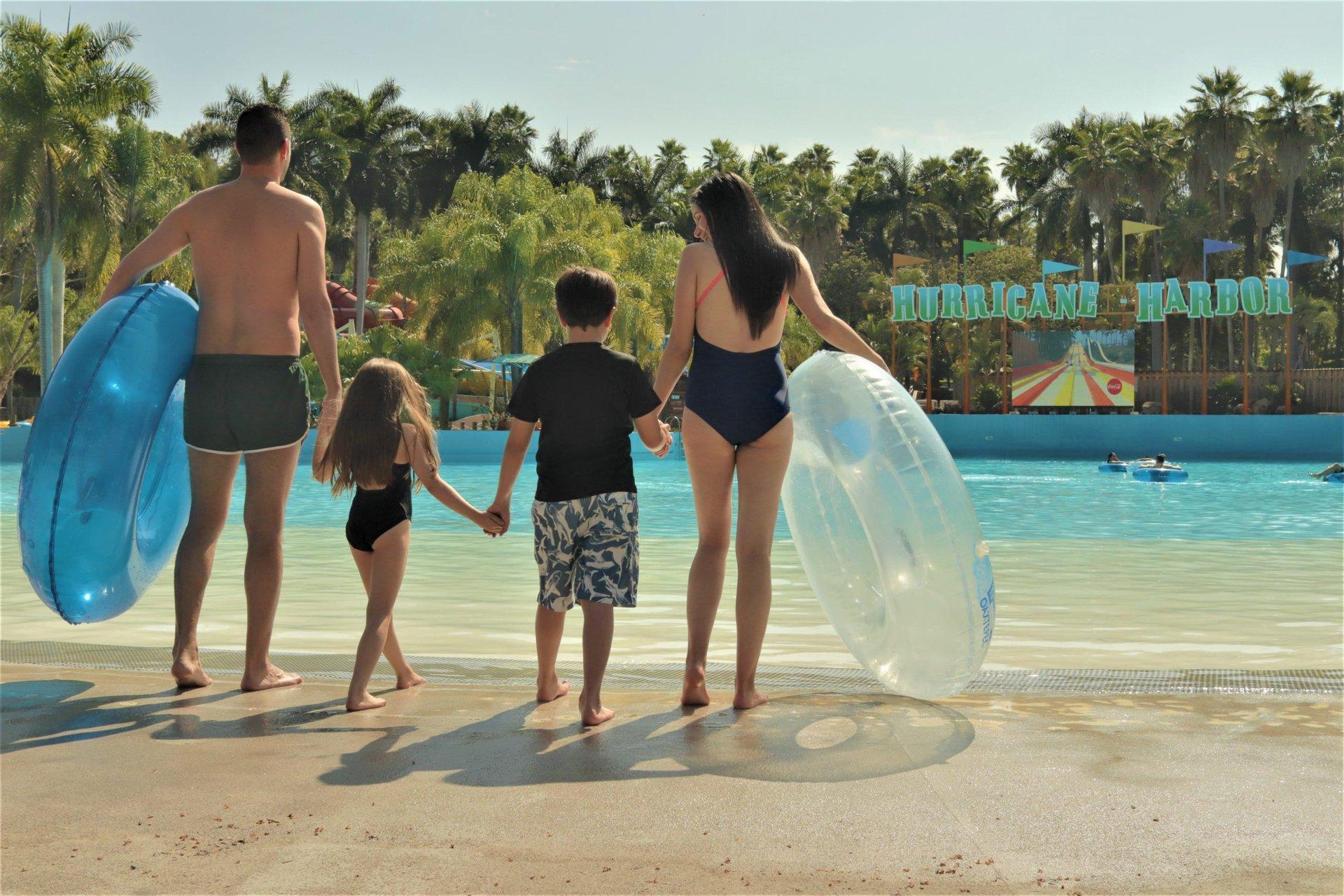 family holding inner tubes at the park
