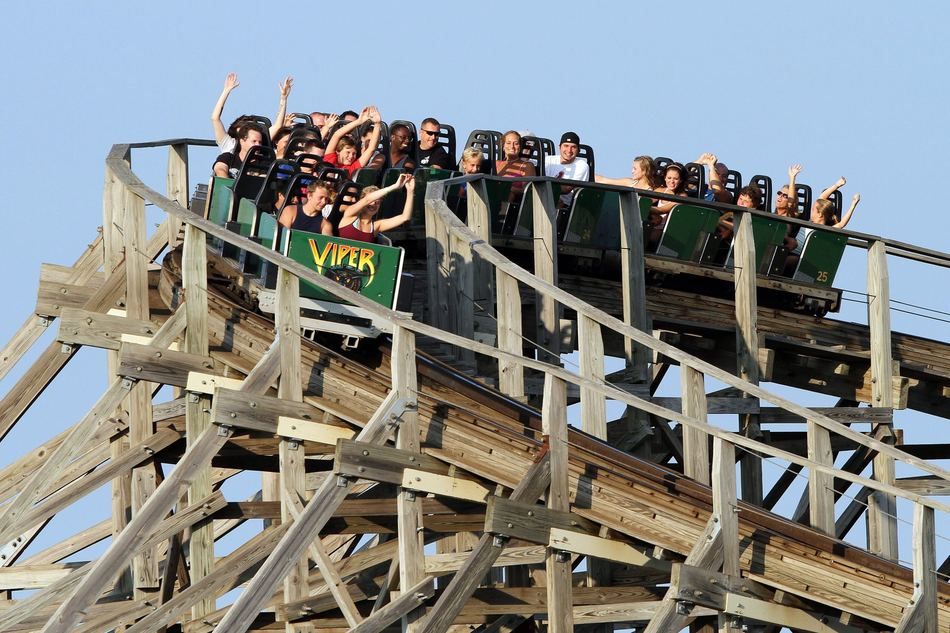 Guests with their hands in the air riding Viper at Six Flags